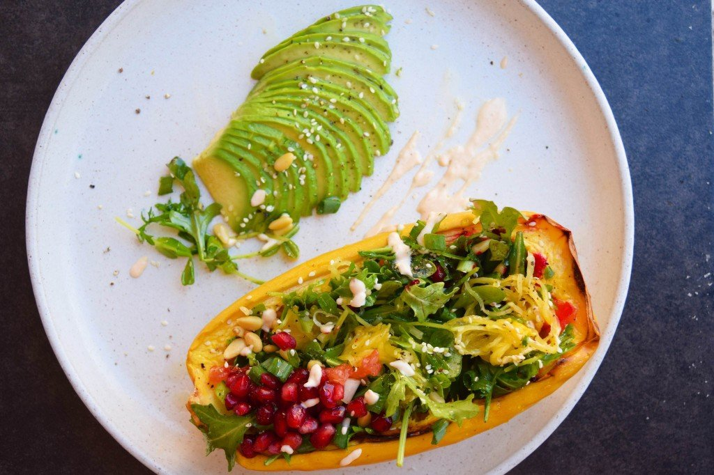 Spaghetti squash salad with a side of avocado on a white plate.