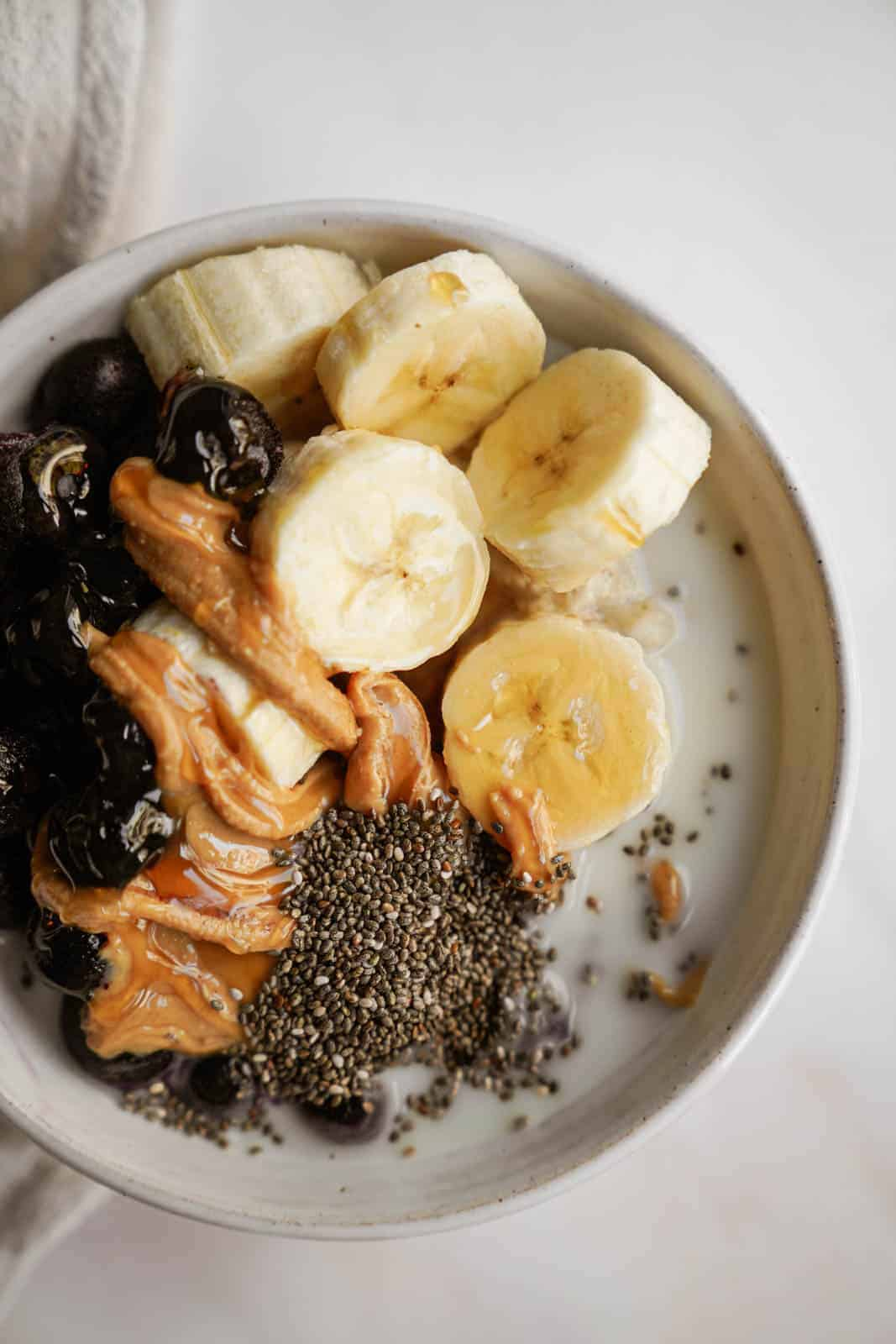 low gi breakfast in a bowl with fruit, peanut butter, and chia seeds on top.