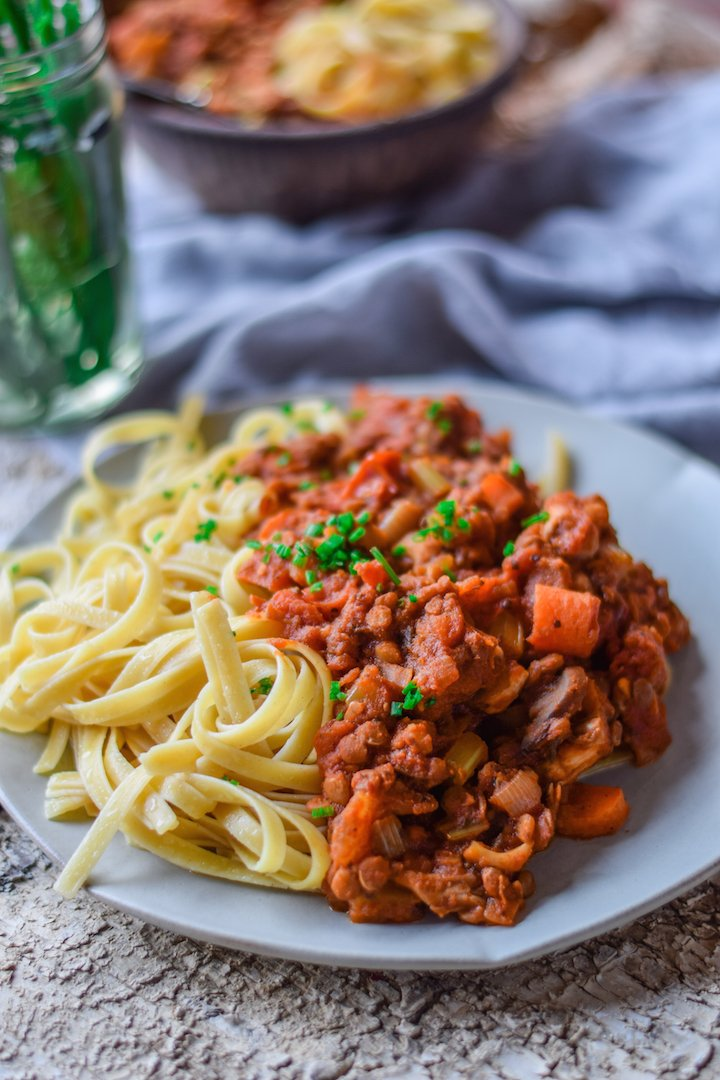 Yummy plant based pasta with deliciously red sauce sitting on serving dish ready to eat.