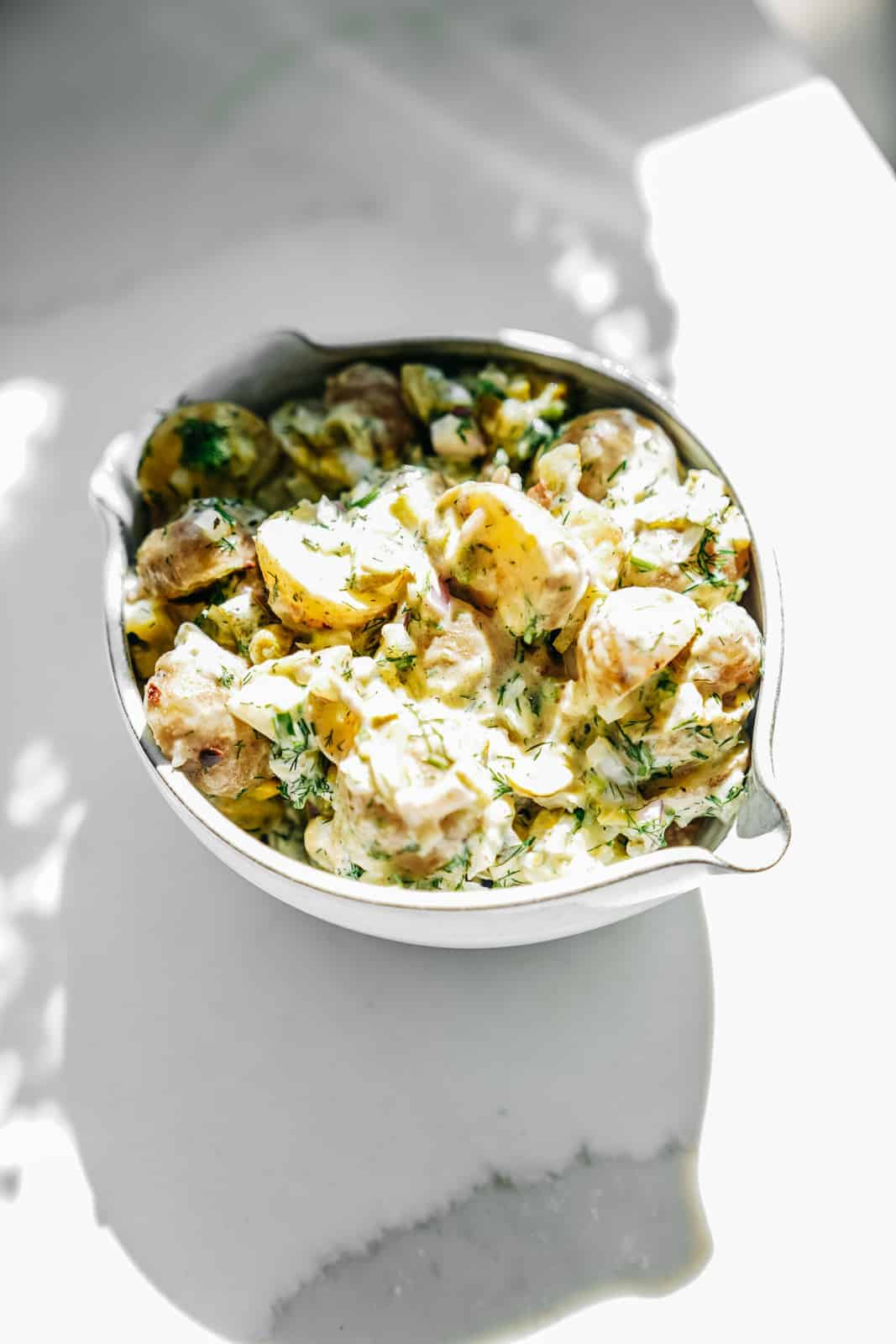 Big white bowl of yummy vegan potato salad.