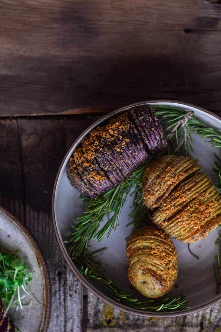 Hasselback potatoes on a plate with fresh herbs