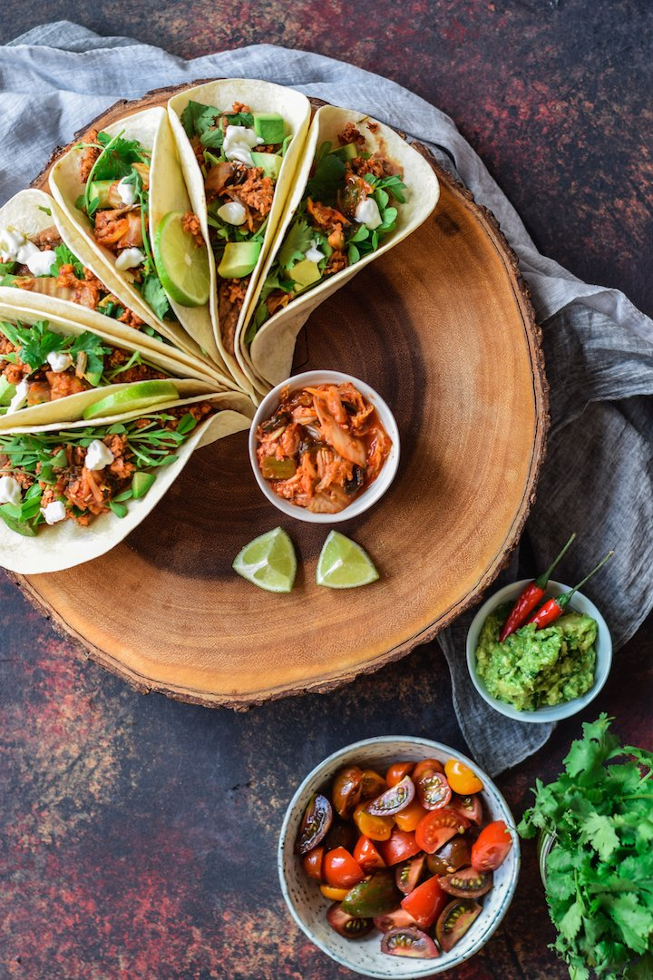 Refried bean tacos perfectly displayed on cutting board with fresh ingredients.