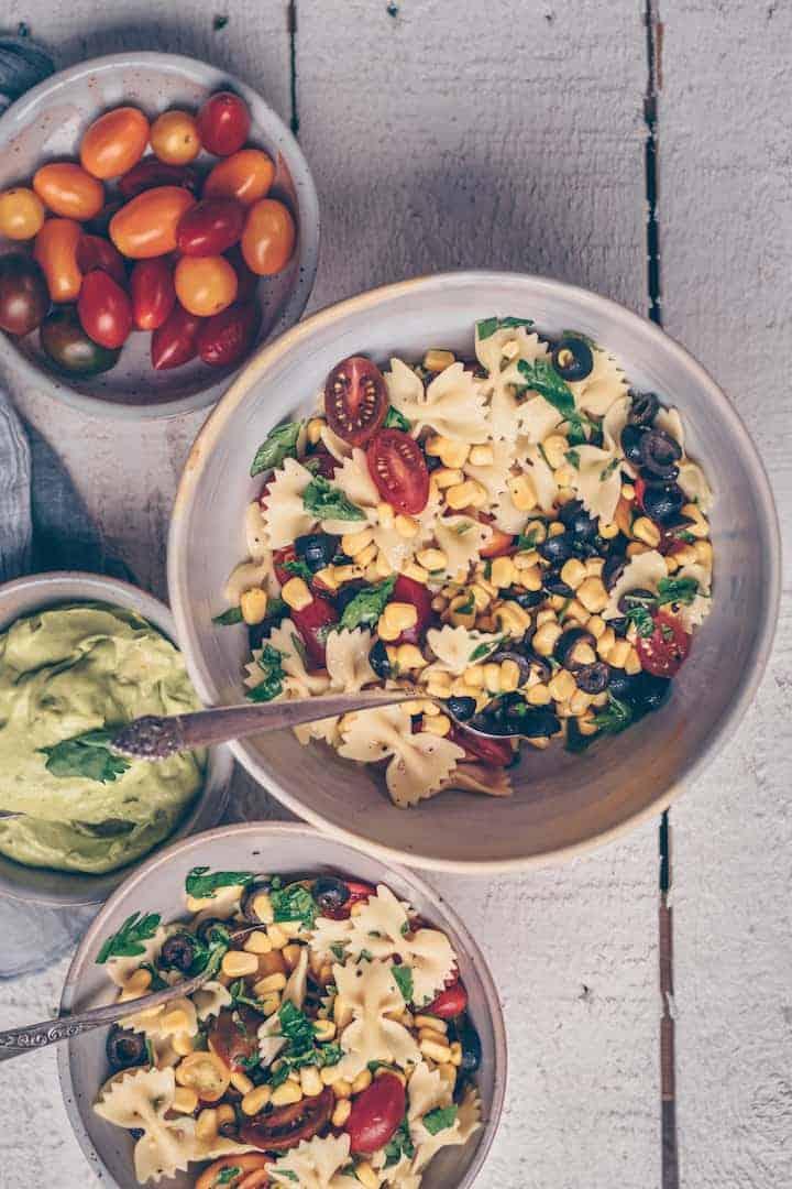 Bowl of Vegan Pasta Salad surrounded by fresh vegetable ingredients