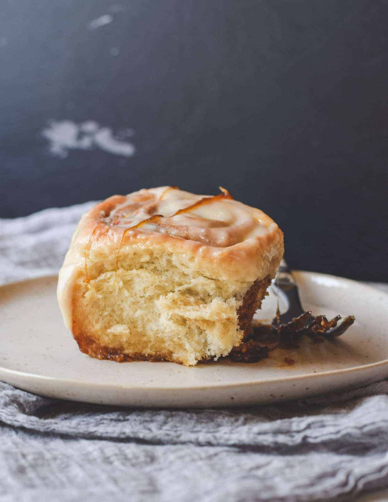 One sticky cinnamon bun on a plate with a fork