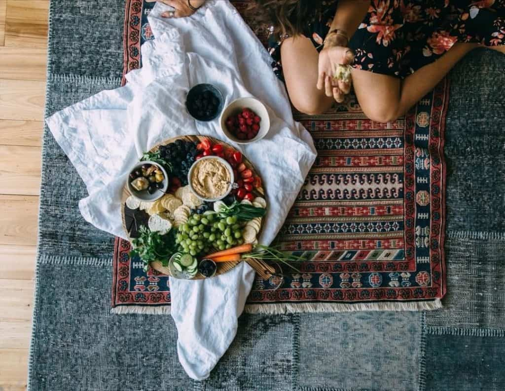 Overhead shot of Maria on carpet with big spread of veggies and lentil hummus.