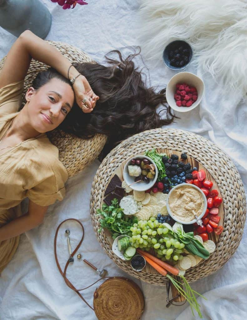 Maria laying down next to a vegetable spread on a cutting board with lentil hummus.