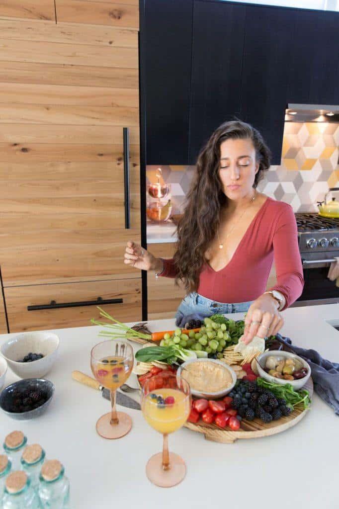 Maria dipping veggies in hummus on a big veggie board.