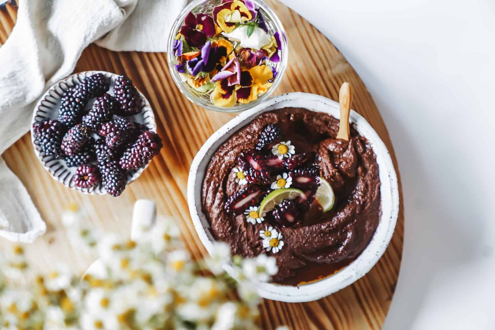 Chickpea Dessert chocolate sauce on a board with fresh fruit and flowers