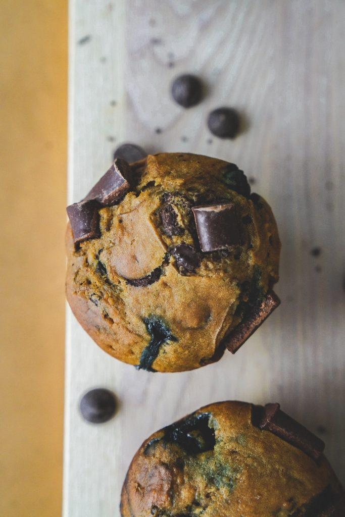 Top shot of a vegan chocolate chip muffin with blueberries with large chunks of chocolate on top.