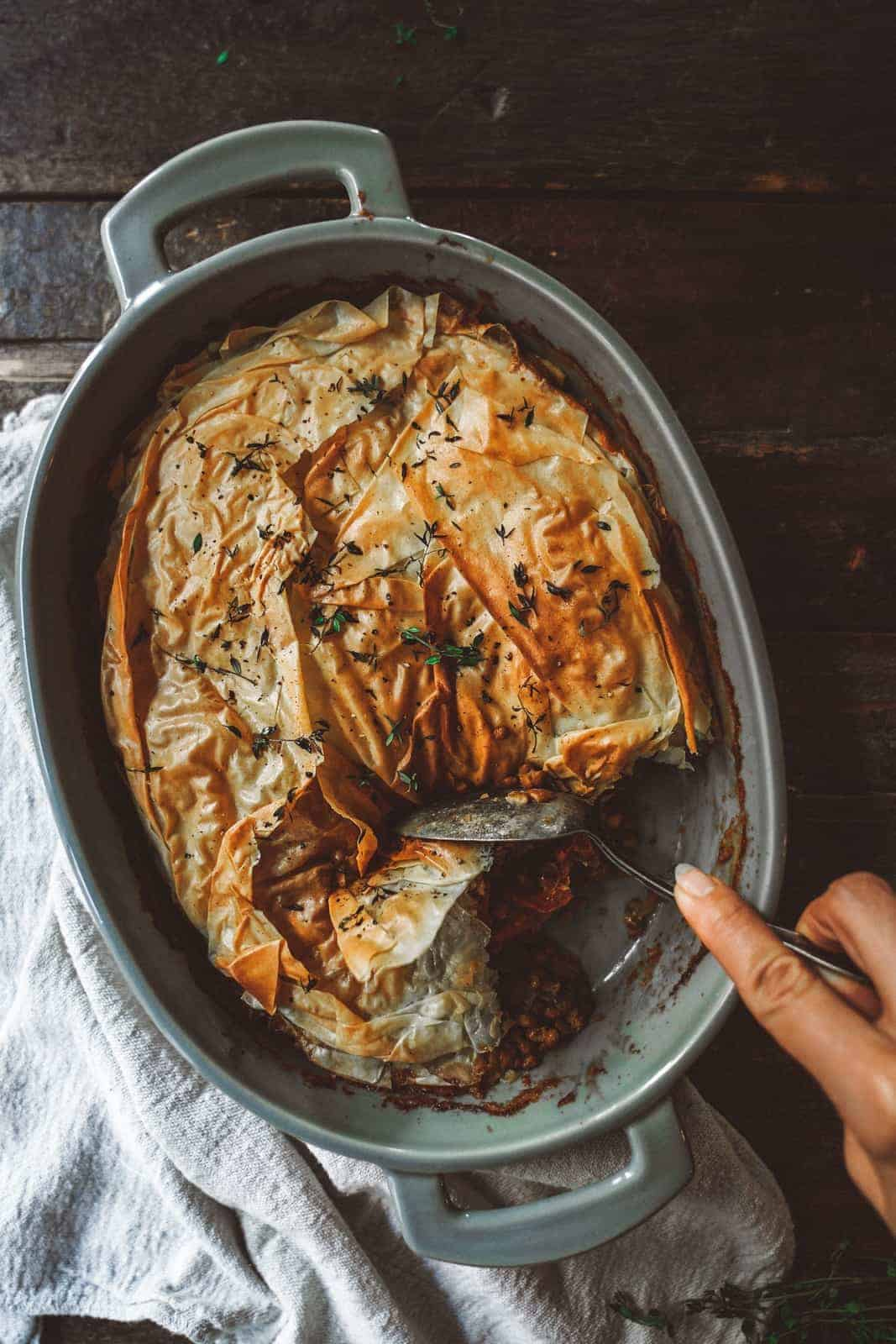 Looking for one of the most comforting recipes to make this September? This phyllo pastry casserole is just that. Big casserole dish on wood table with spoon digging into casserole.