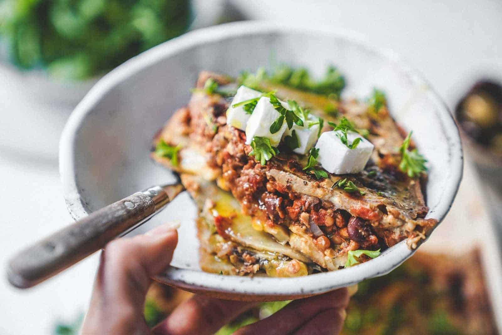 A bowl of delicious vegan moussaka topped with fresh herbs and vegan feta cheese.