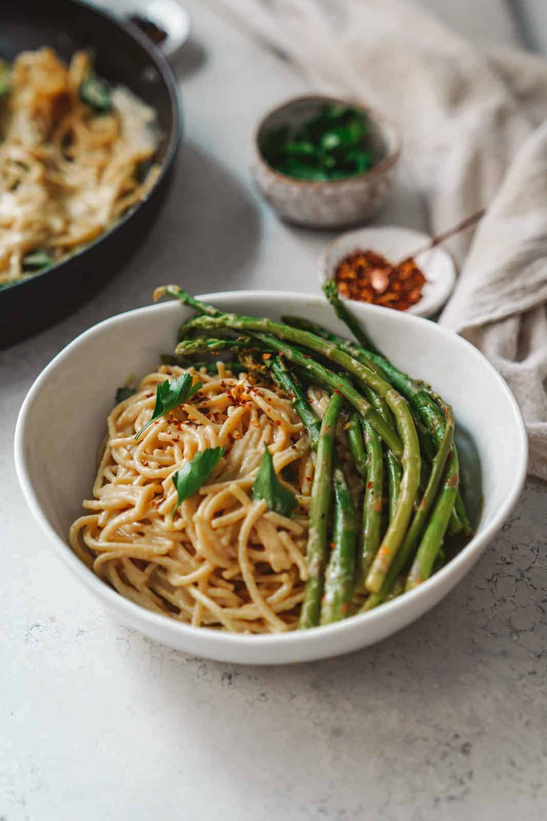 Bowl of spaghetti with vegan white wine sauce + asparagus on table.