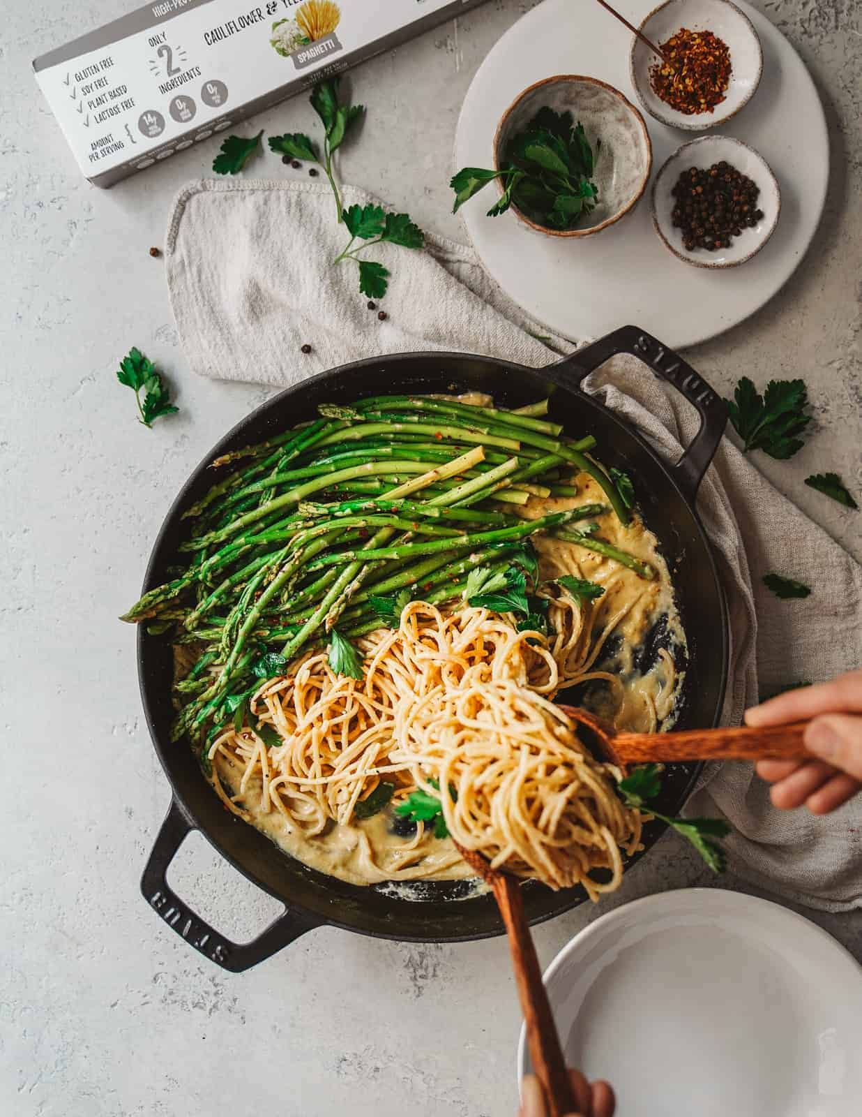 Big pan of spaghetti with asparagus and white wine spaghetti sauce sitting on table with ingredients in background.