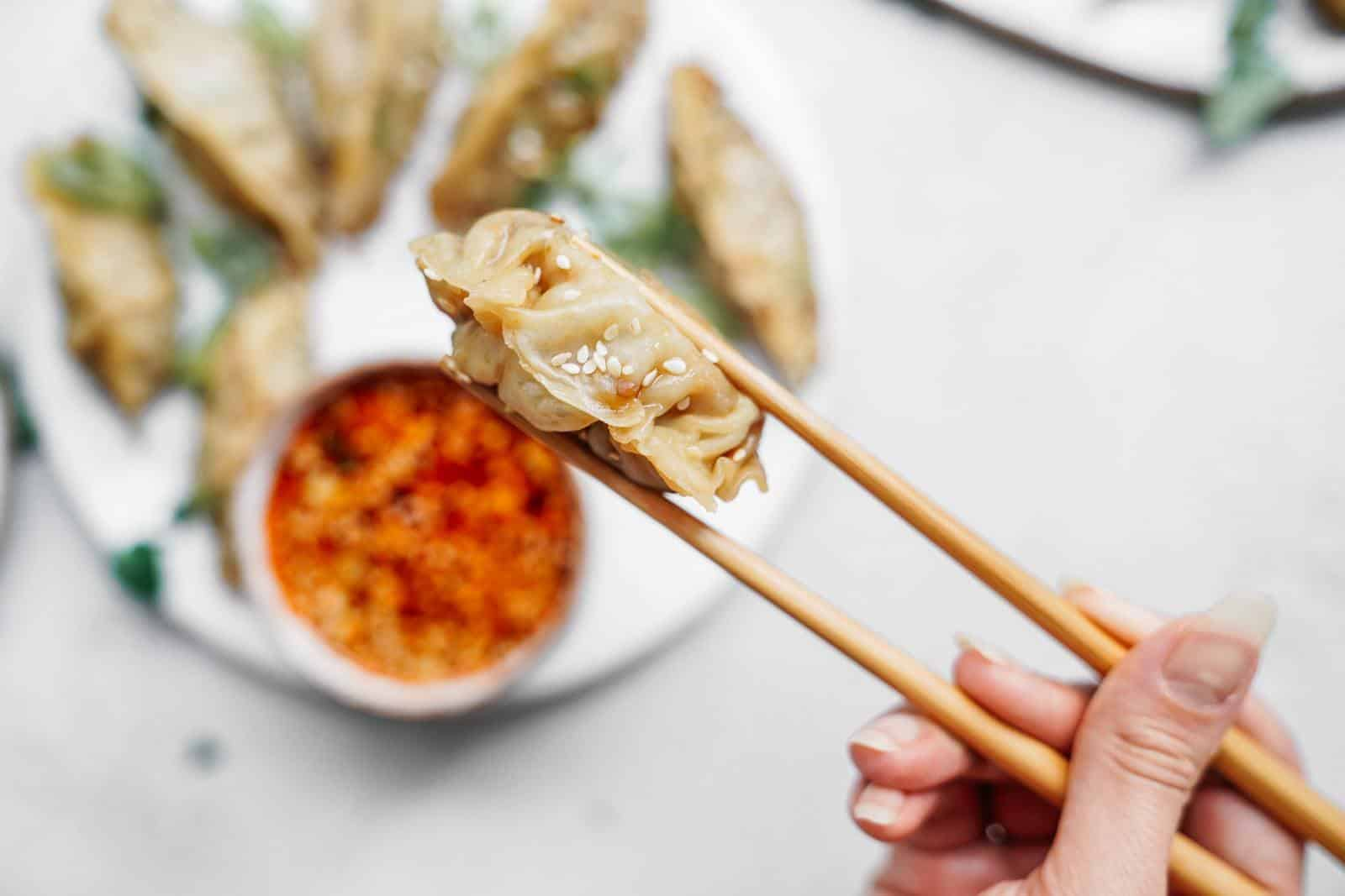 Vegan dumplings on a plate in the background on a table, with a close-up of a vegan dumpling in between chopsticks.