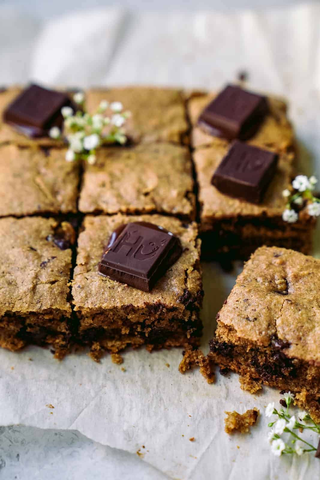 Vegan Blondies cut into pieces with chocolate chunks.