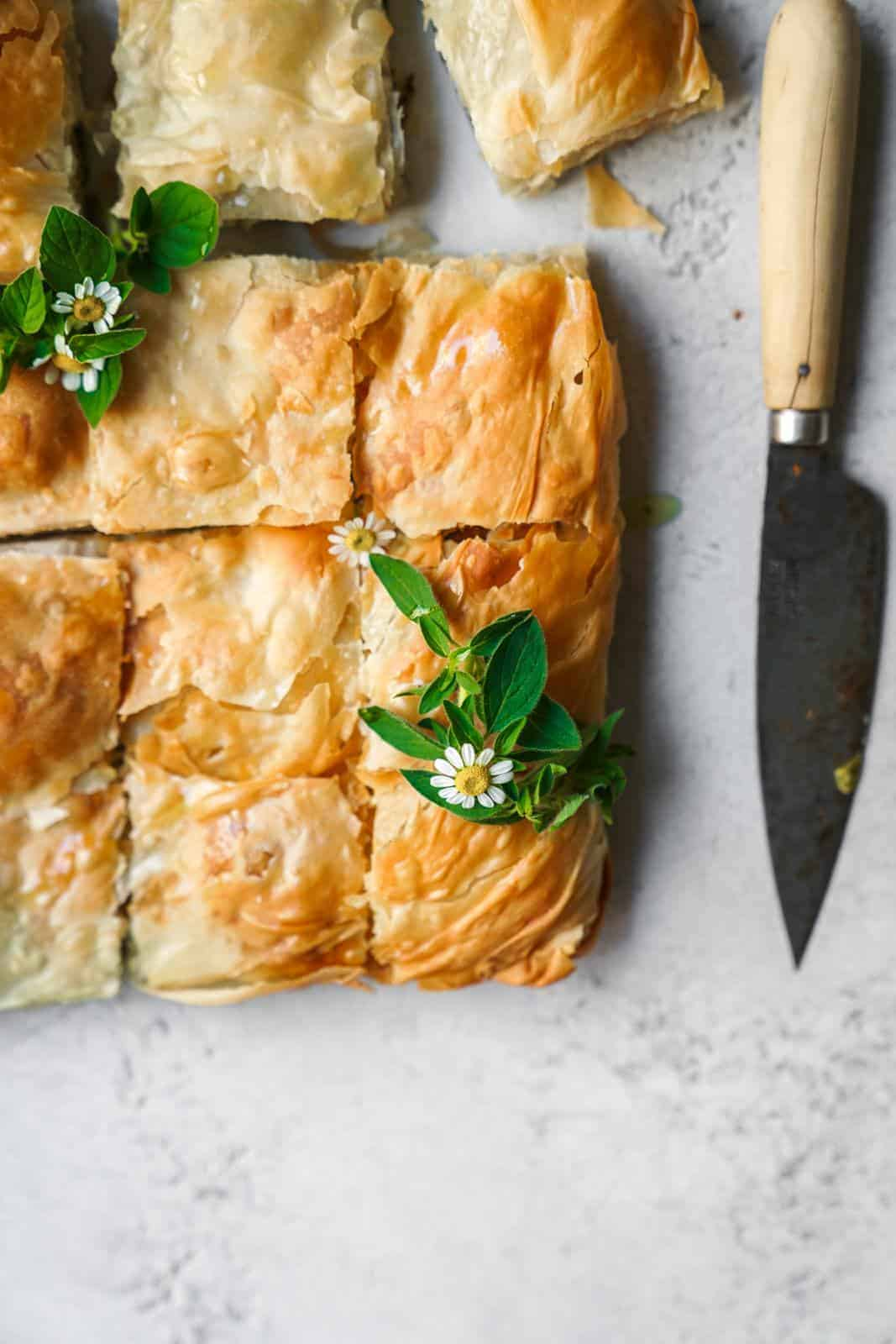 Close-up of vegan spanakopita sliced with knife beside it