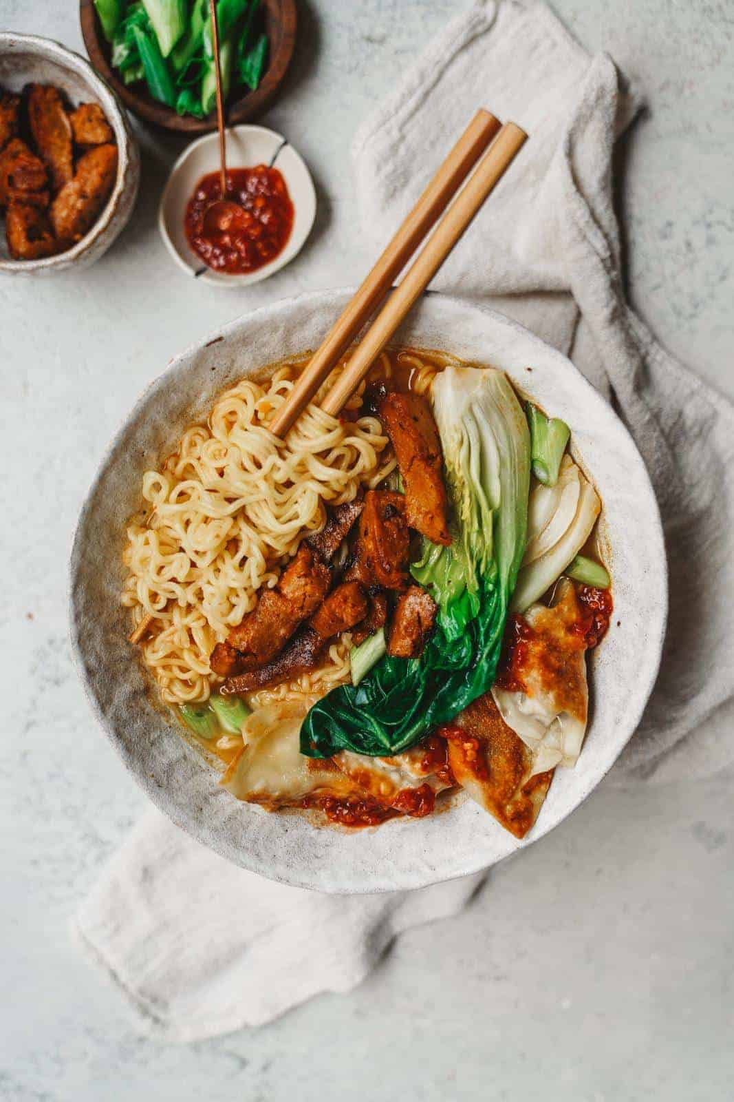 Creamy vegan ramen sitting on countertop with chopsticks bursting with colour from the toppings