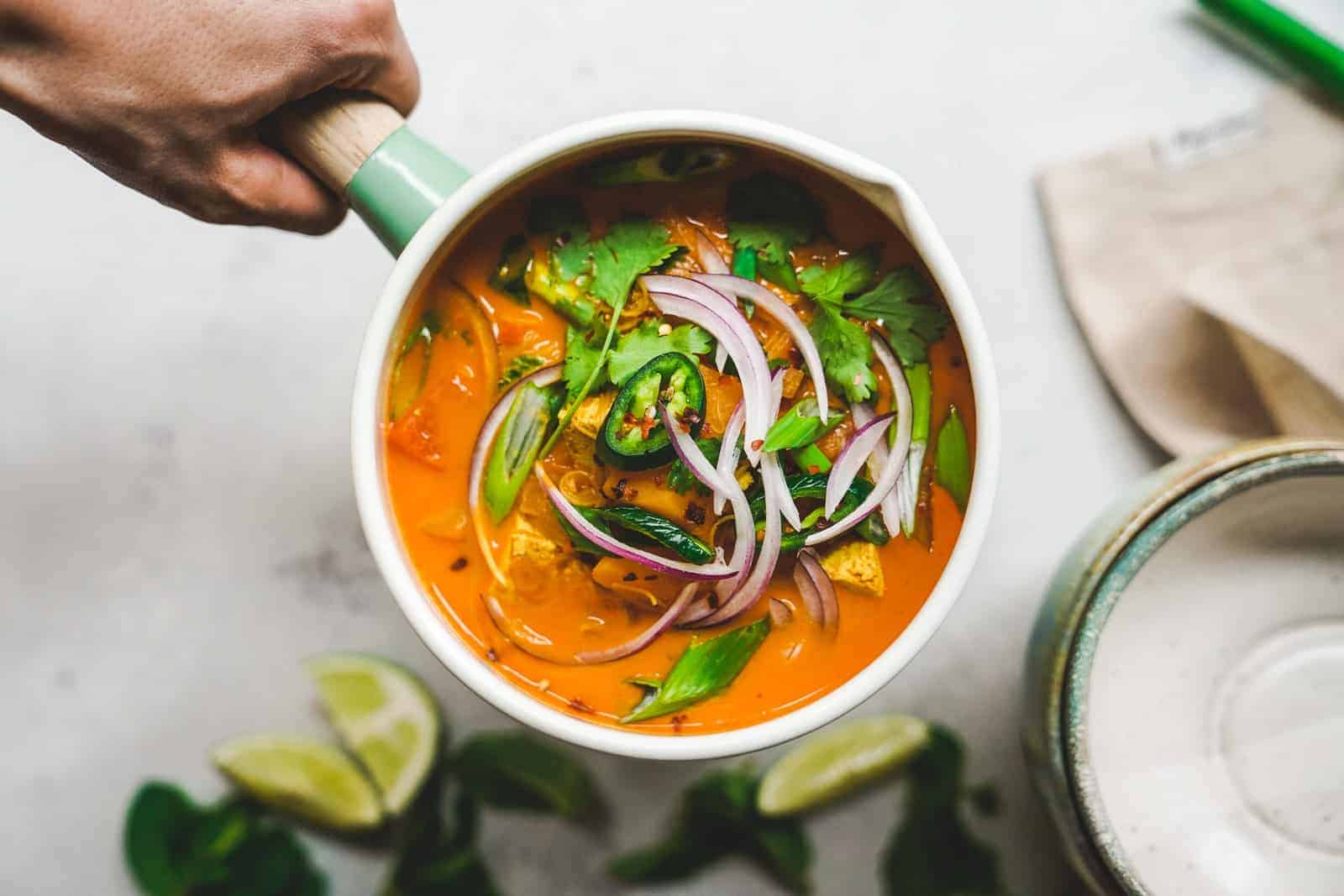 A pot with bright orange curry with toppings of fresh herbs and red onion.