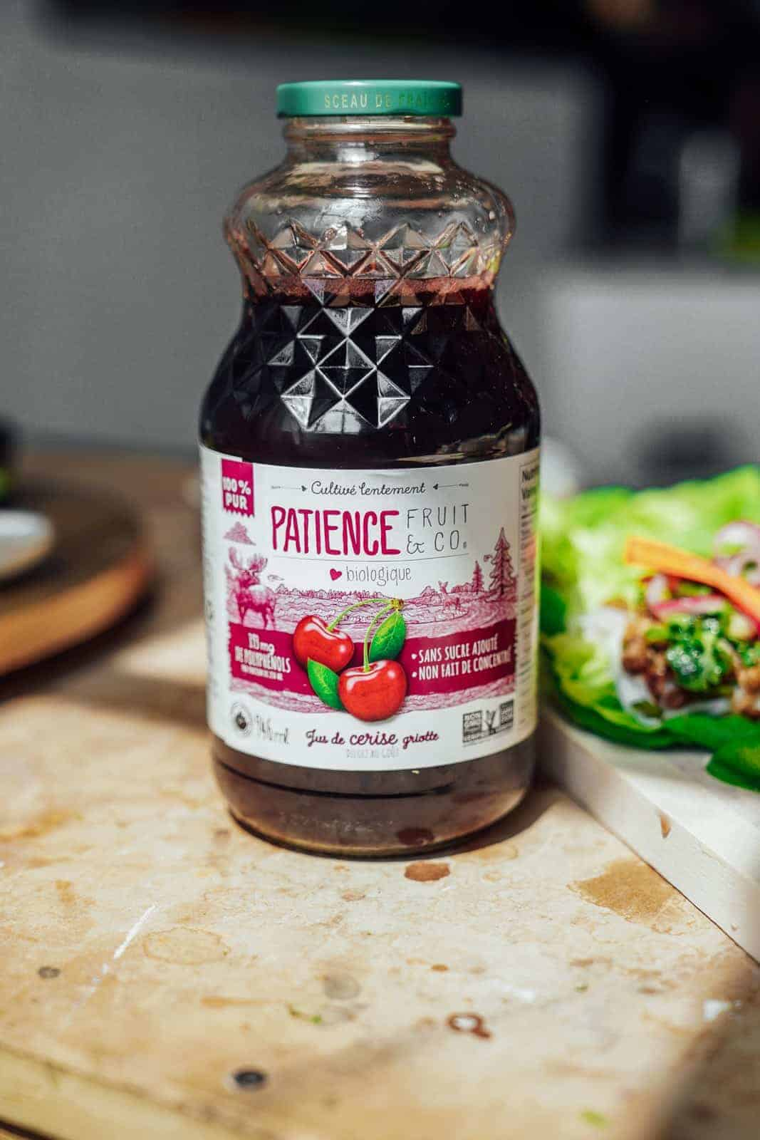 Bottle of Patience Fruit & Co. Cherry Juice sitting on countertop with lettuce wraps in the background.