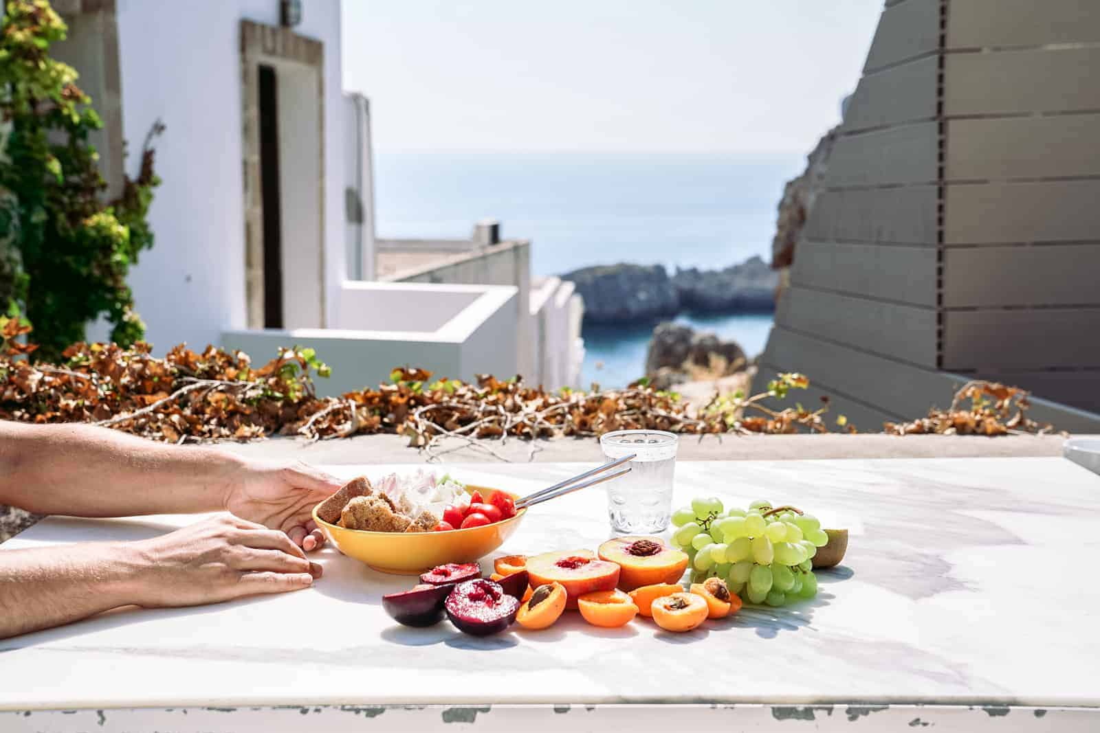 Healthy salad and fruit on a table overlooking Mykonos, Greece.