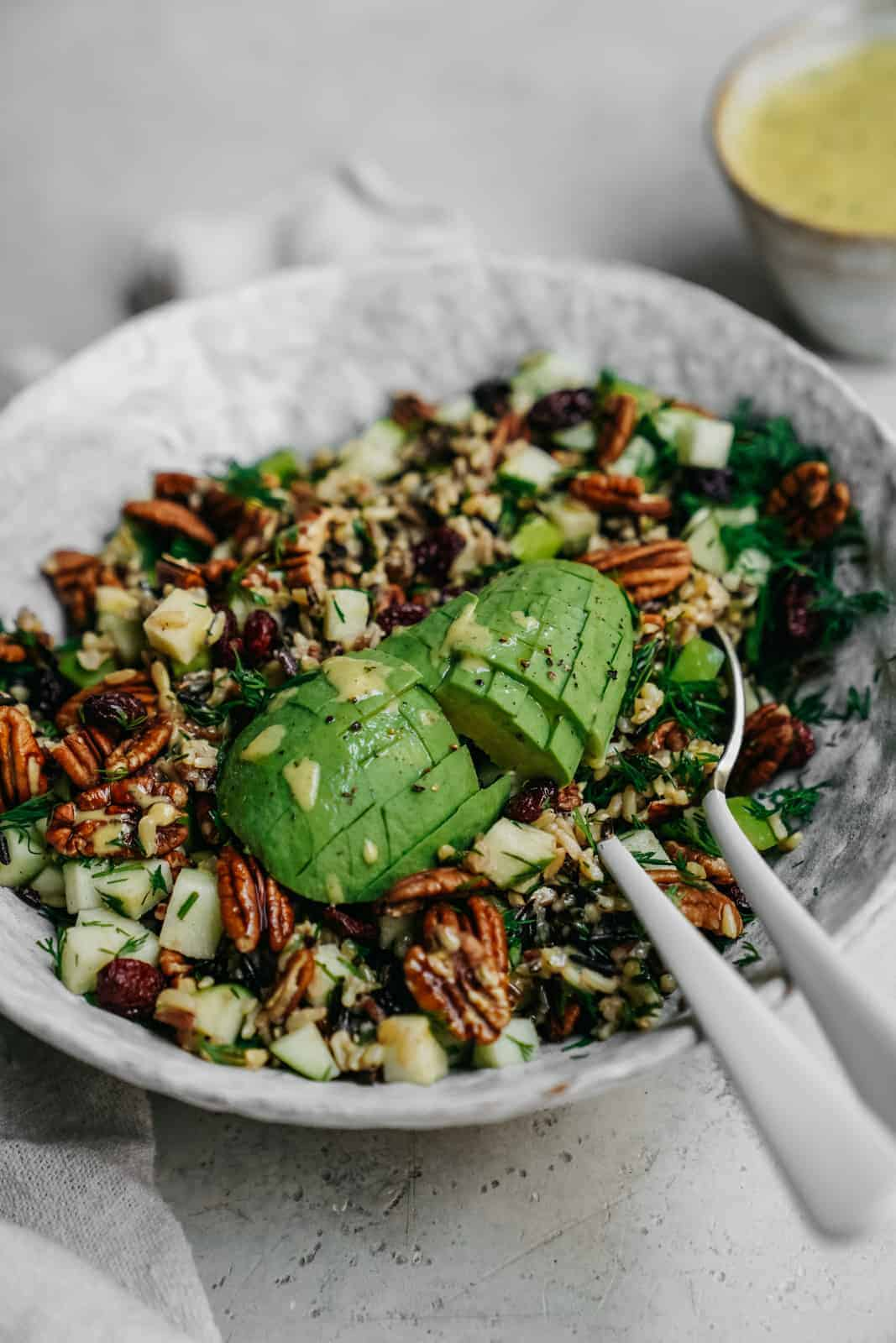 Easy Vegan Simple Wild Rice Salad sitting on counter with serving spoons in the dish and deliciously ripe avocado. A perfect salad for high protein vegan meal prep.