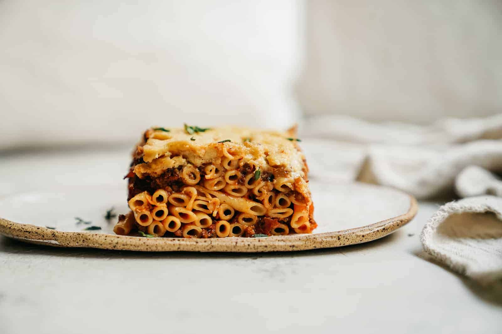 Side of Greek Pastitsio on white plate.