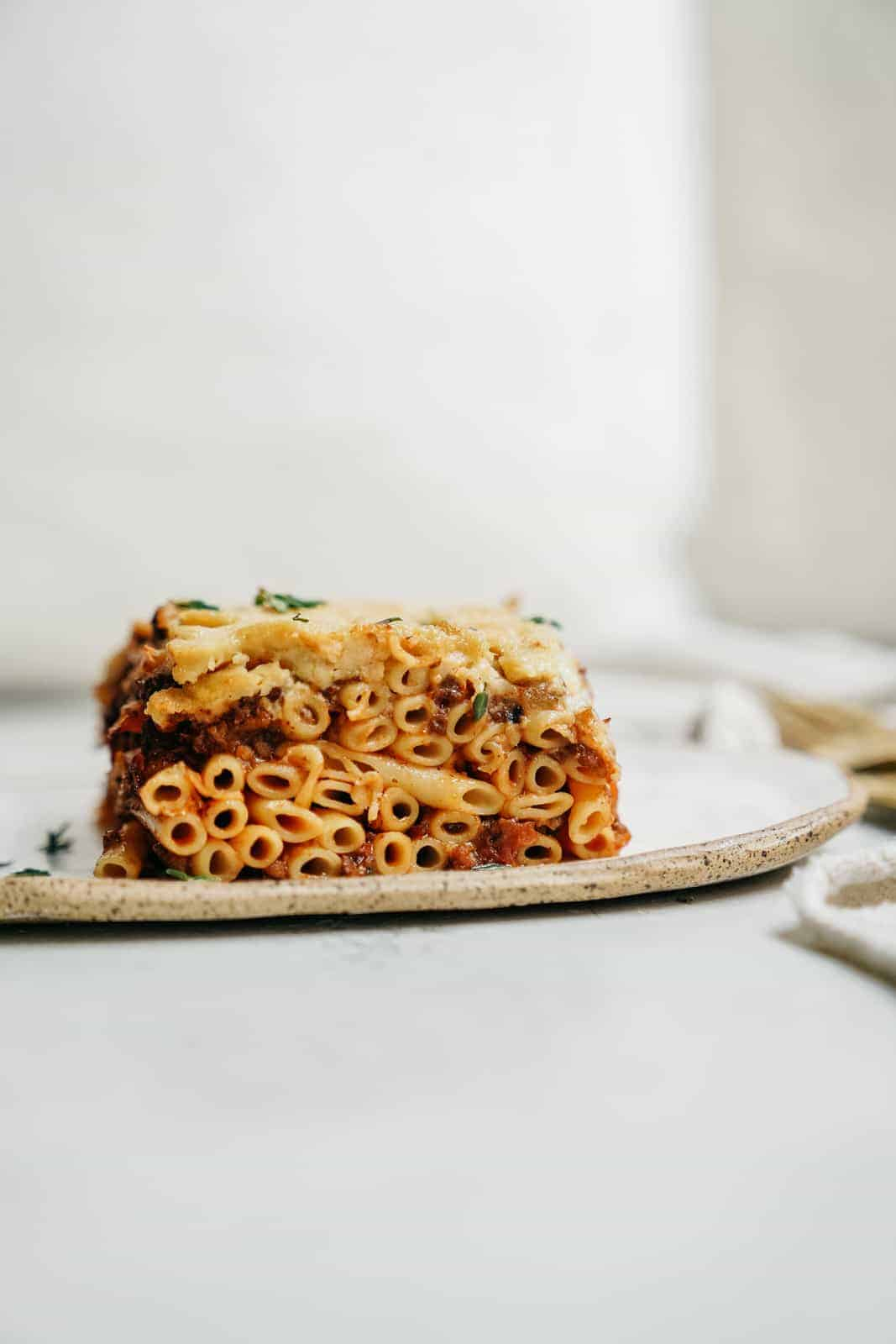 Side angle of Greek Pastitsio on a white serving plate.