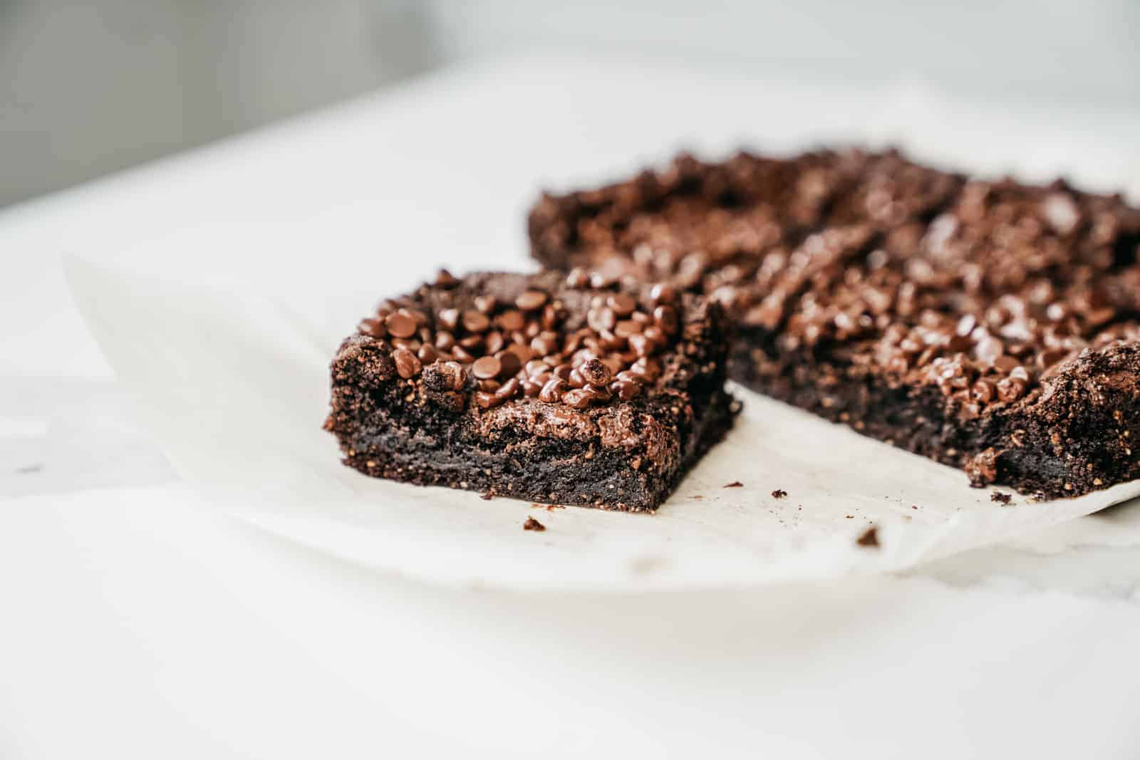 Almond Flour Brownies on a plate on the counter with one cut out of the batch.