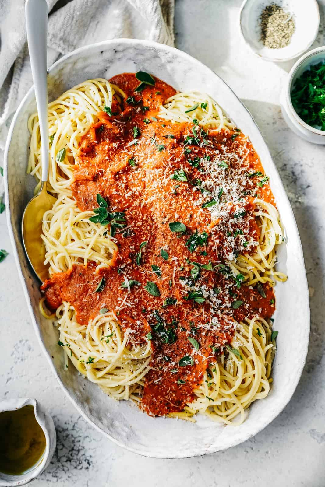 Big serving dish of Spaghetti with Vegan Pasta Sauce and vegan parmesan cheese sprinkled on top.