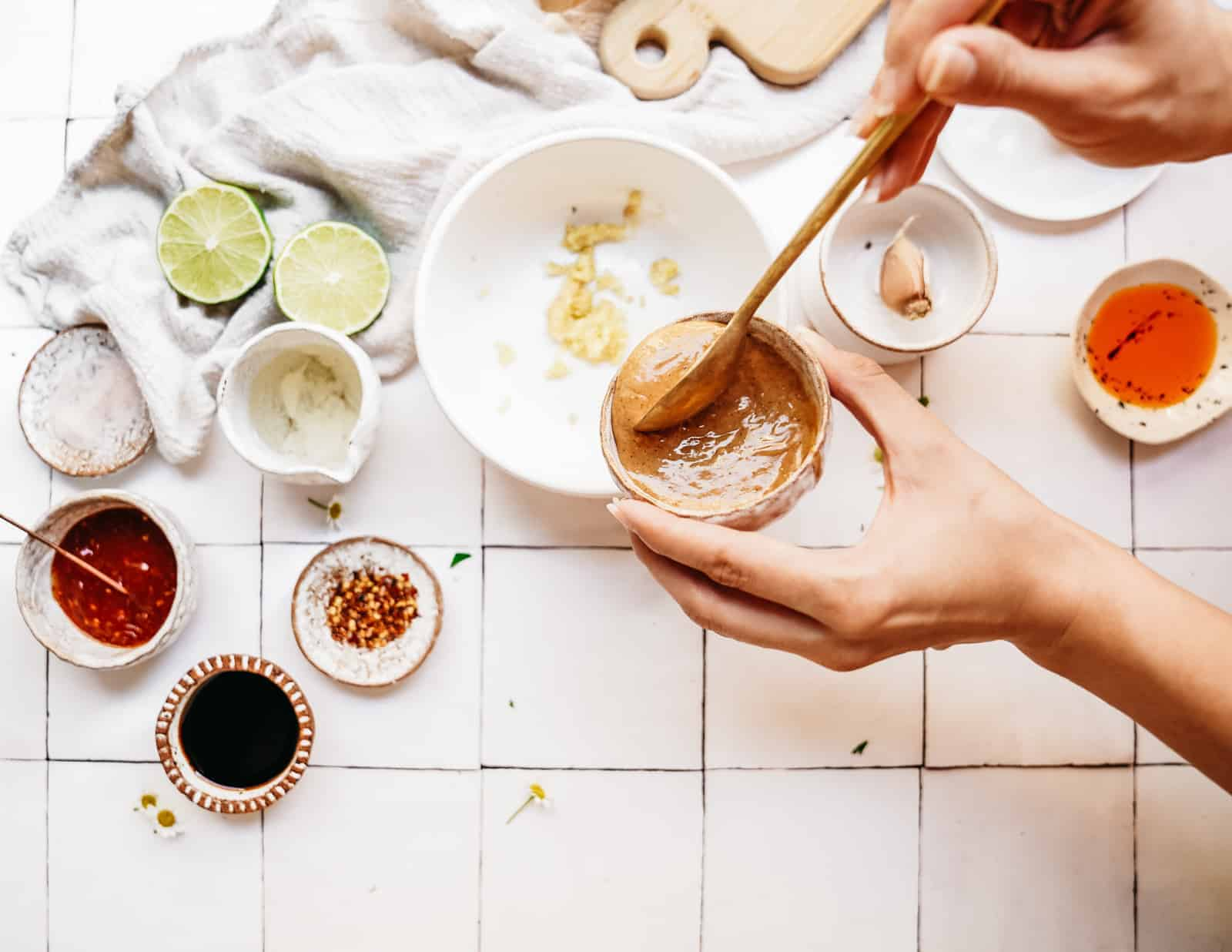 Person showing you how to make peanut sauce in a bowl on a white countertop