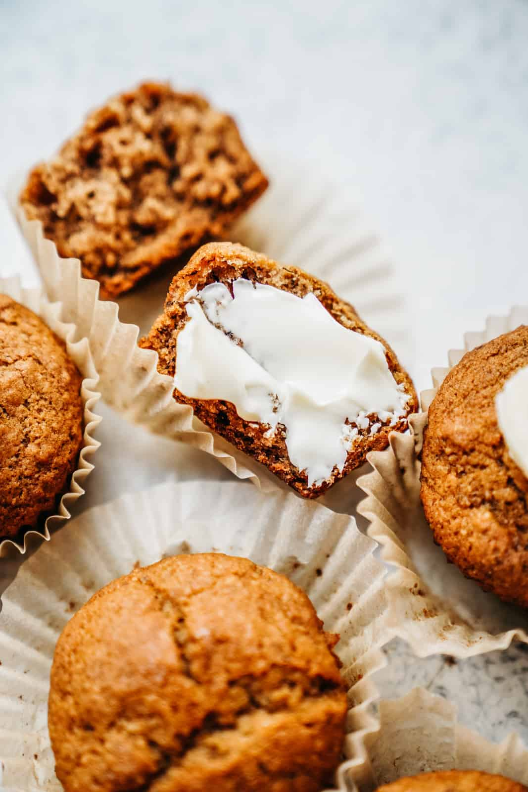 Close-up of Banana Muffins with vegan butter smeared on a cut muffin.