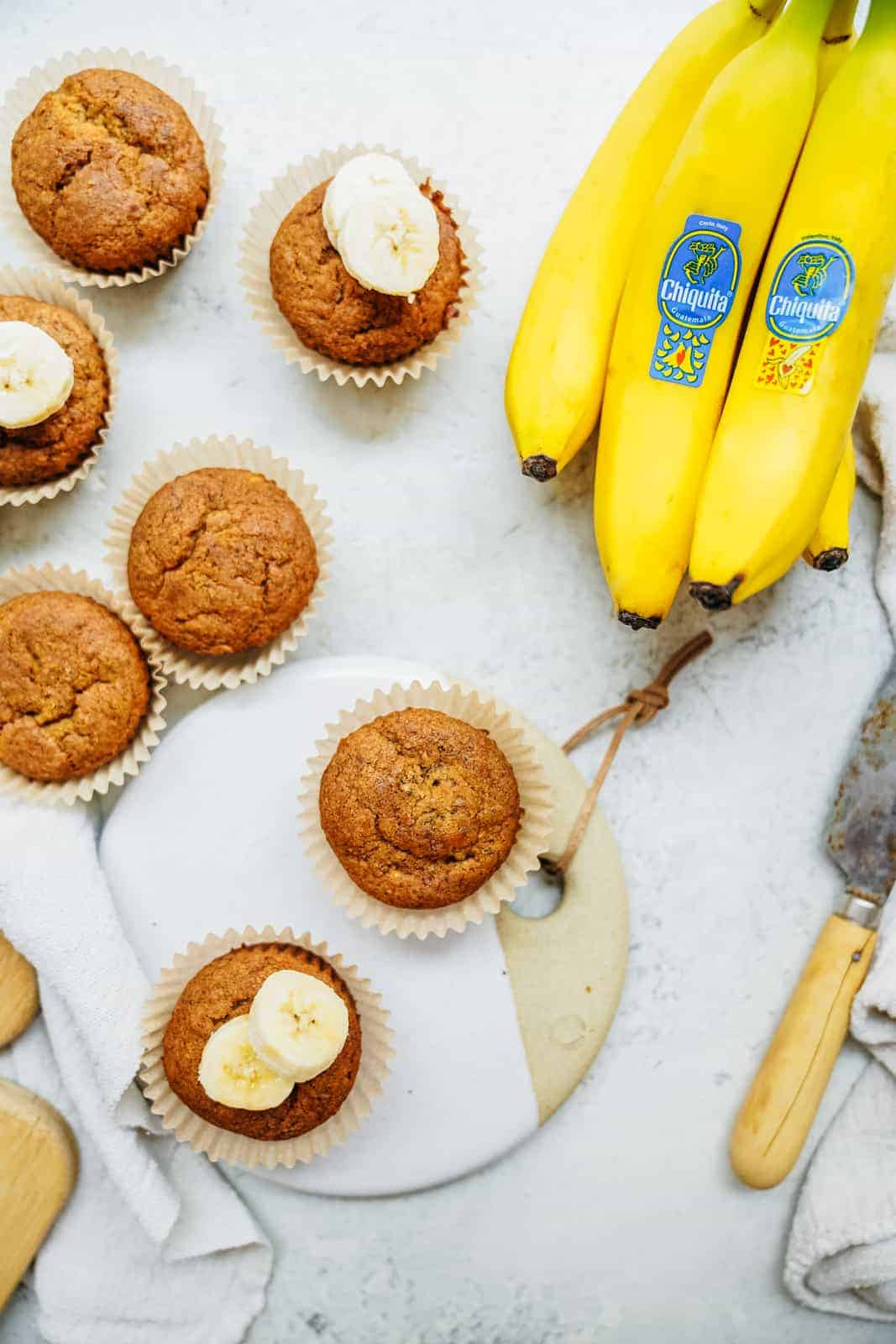 Quick and easy vegan banana bread muffins scattered on countertop with a bunch of fresh yellow bananas.