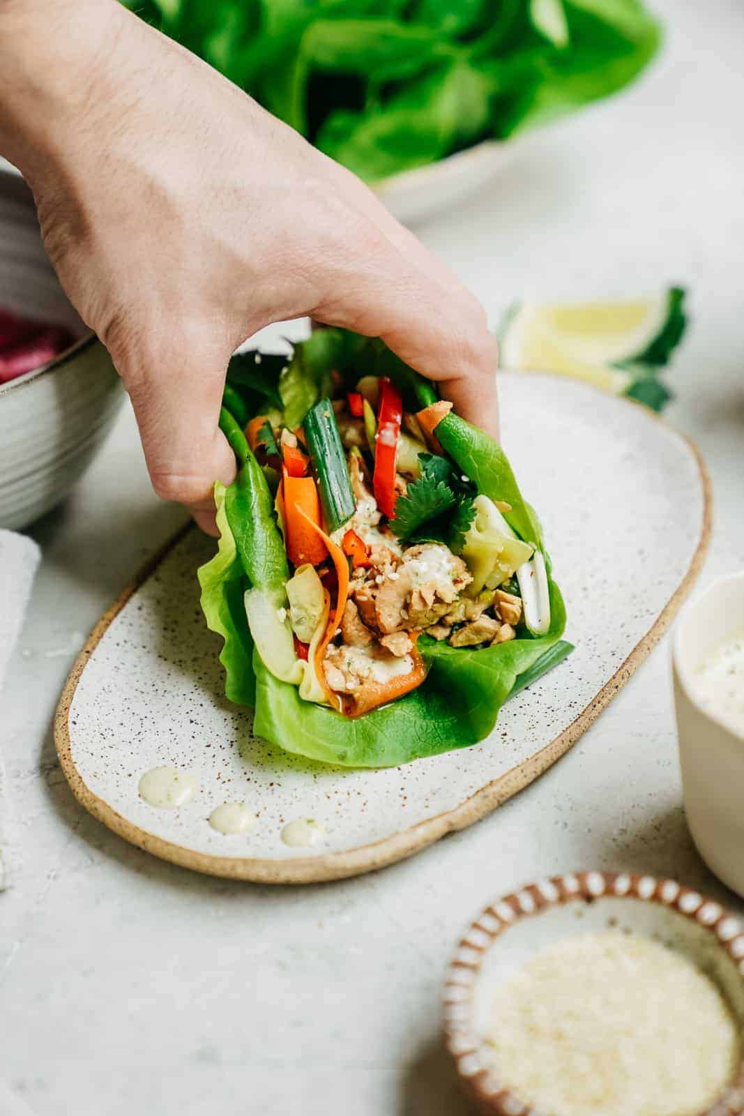 A hand grabbing a vegan tuna lettuce wrap off a plate.
