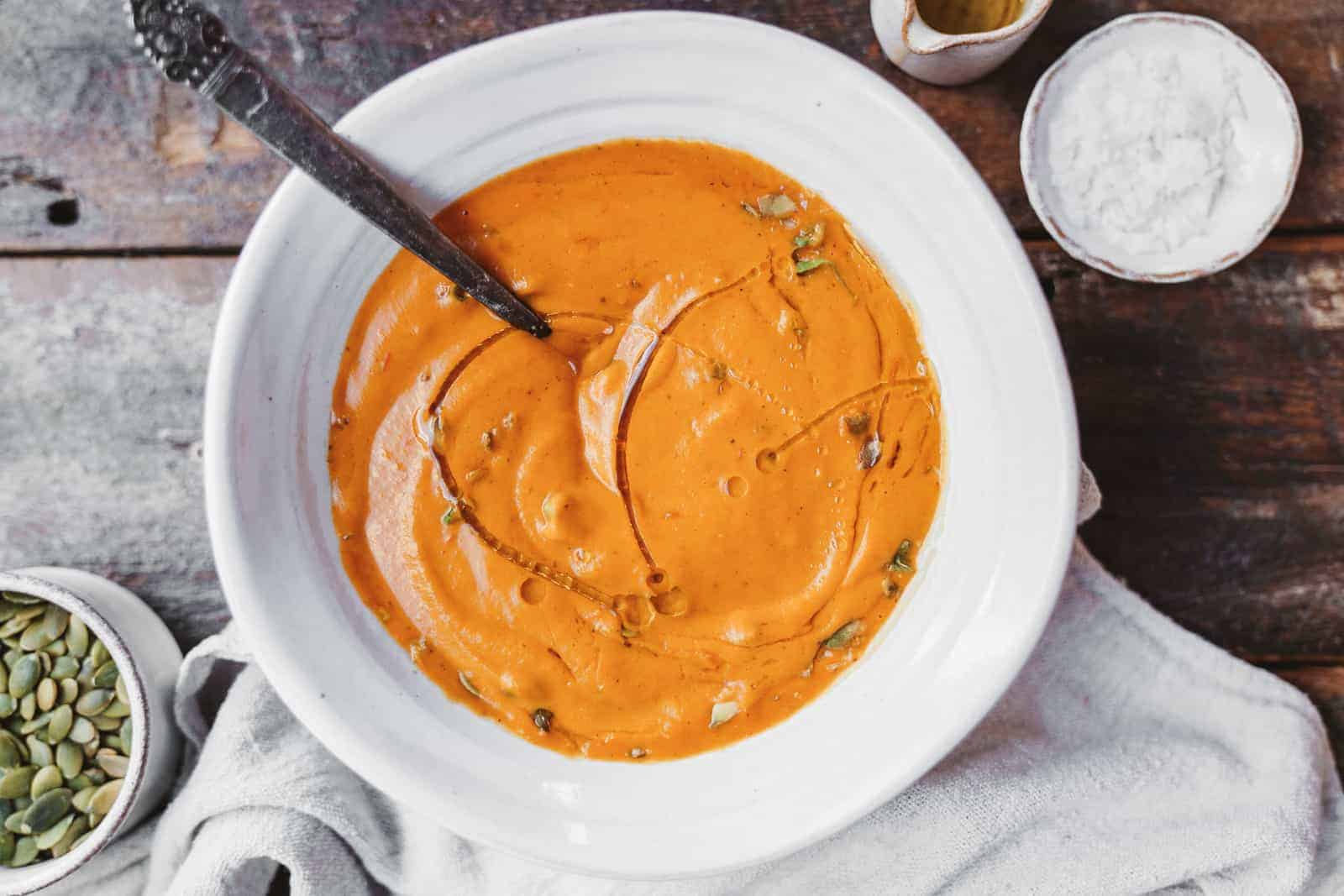 A big bowl of bright orange carrot soup with a drizzle of olive oil. Vegan, and dairy-free.
