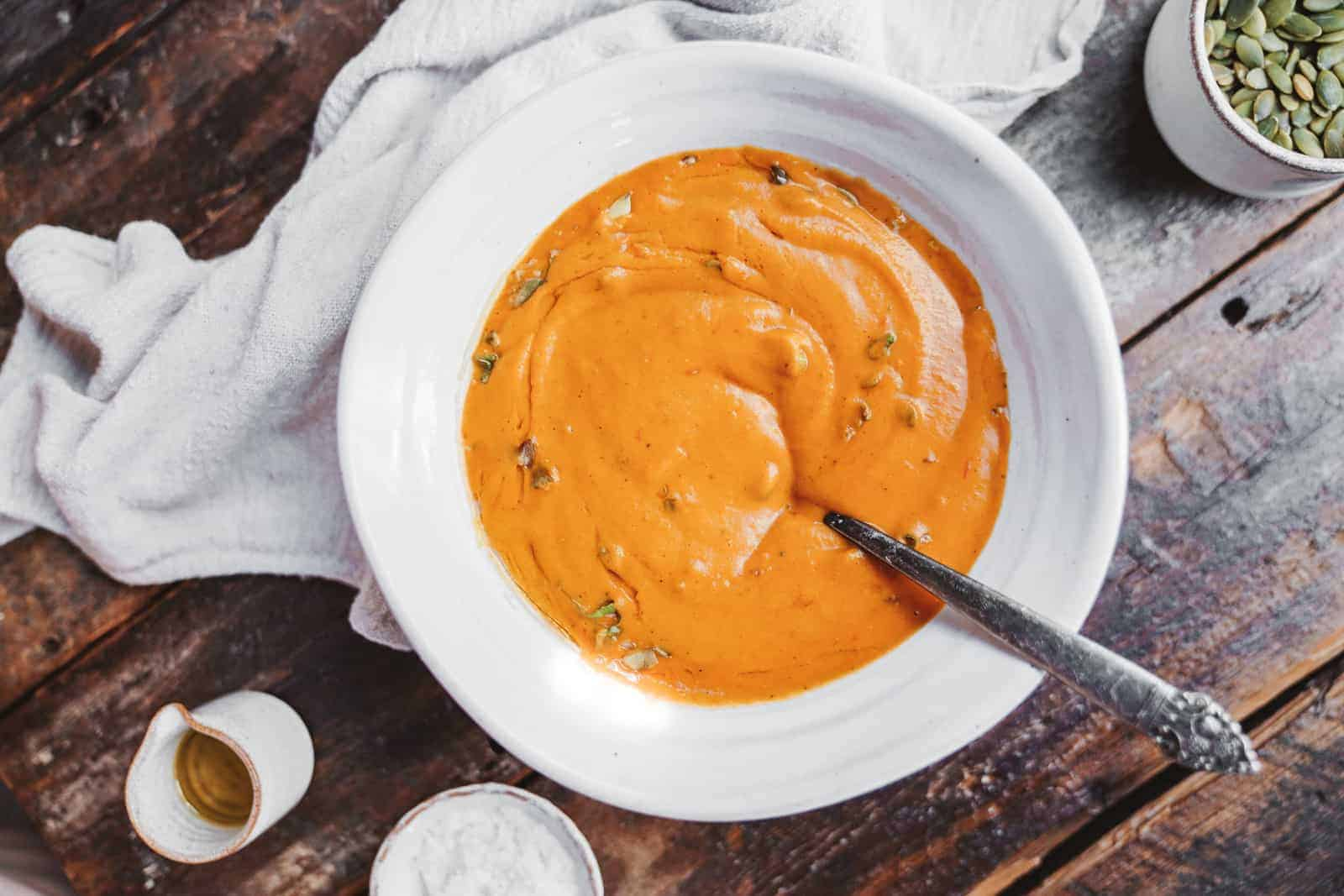 A spoon in a big bowl of creamy vegan carrot soup ready to be devoured at the table.