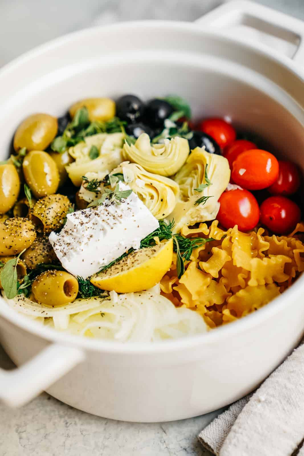 Close-up of a big pot with all the ingredients for a one pot greek pasta. One of my favorite, easy, vegan meals.