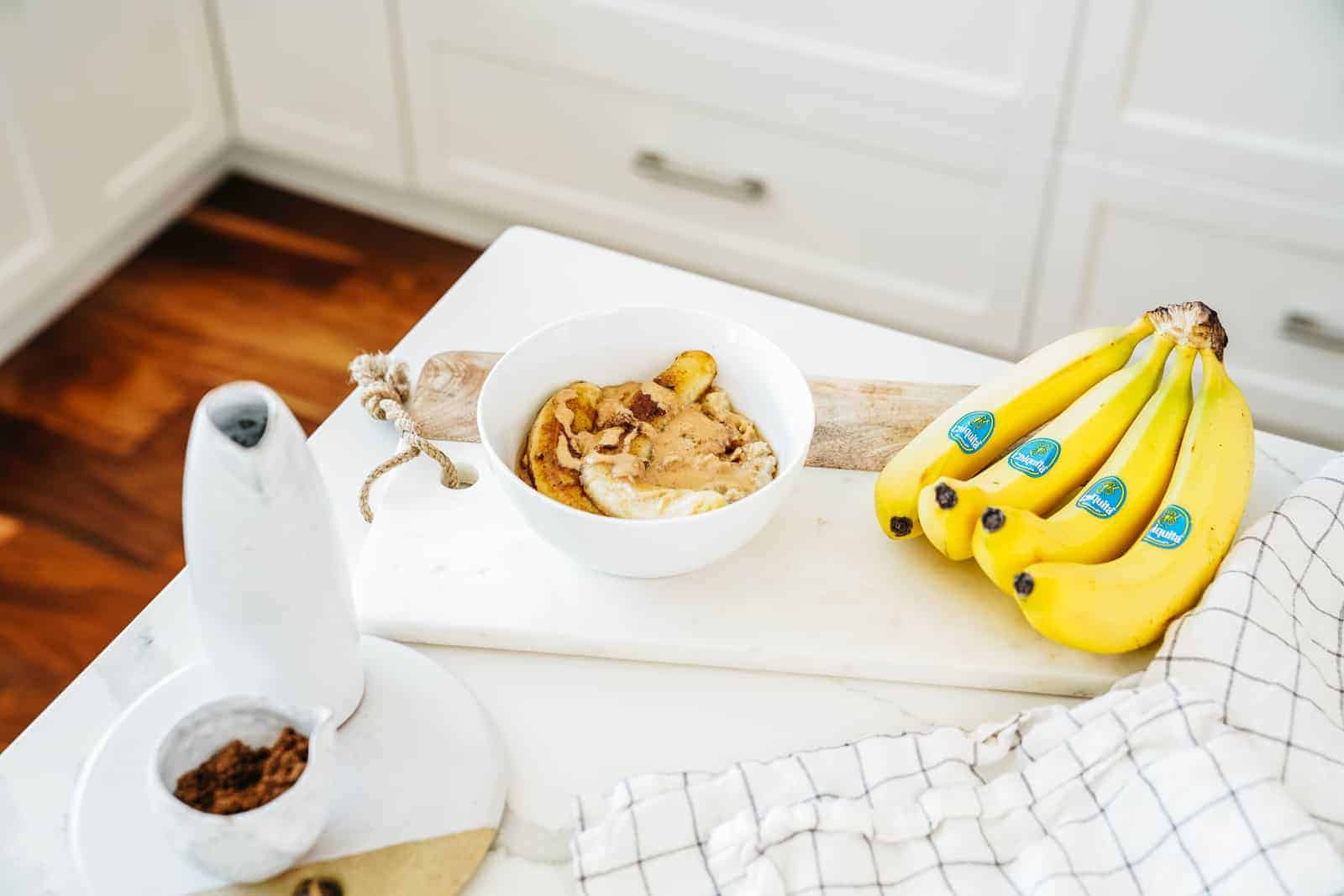 Countertop with bananas and bowl of fried banana recipe on top of oatmeal.