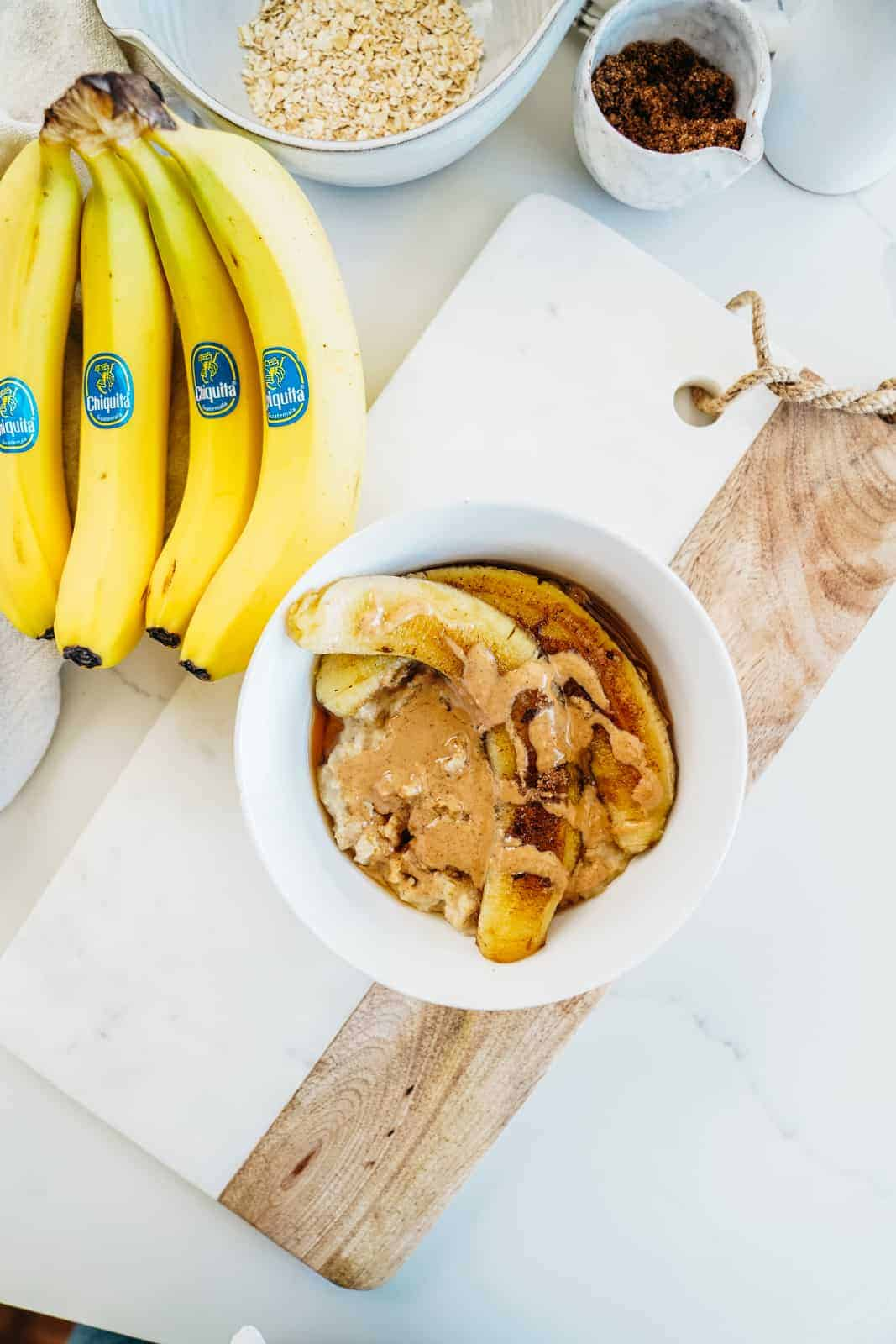 Chiquita Bananas next to cutting board with a bowl of fried banana oatmeal.