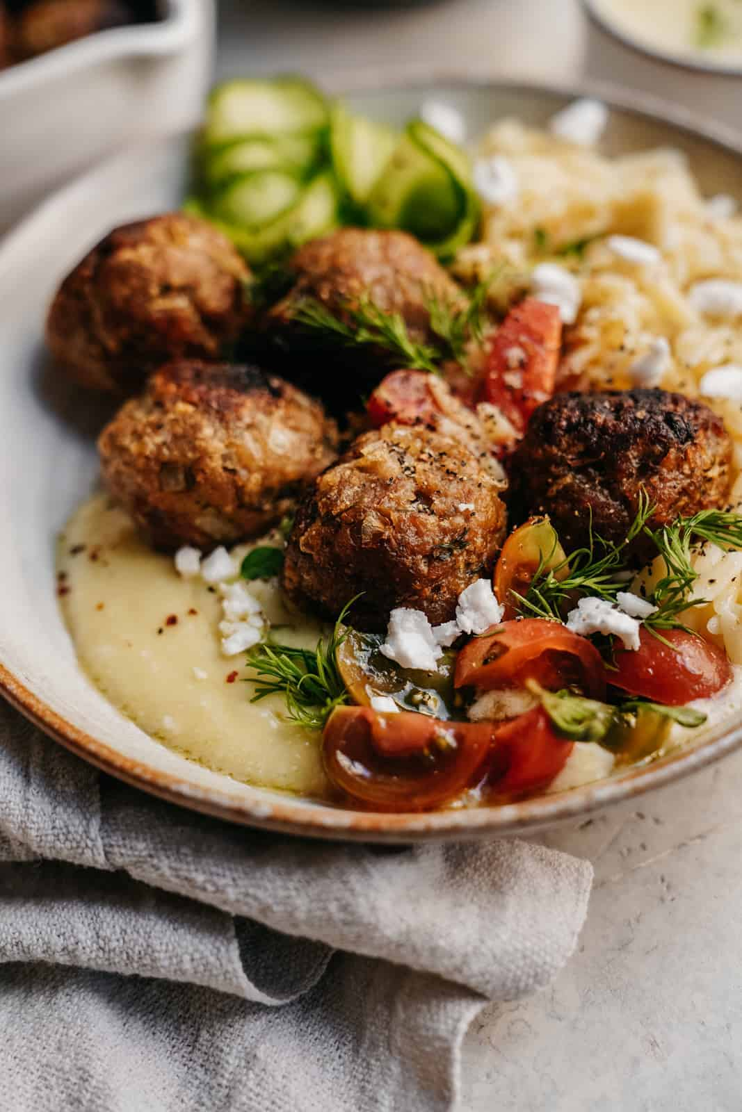 Close-up of Greek meatballs on a dish with creamy hummus and fresh herbs.