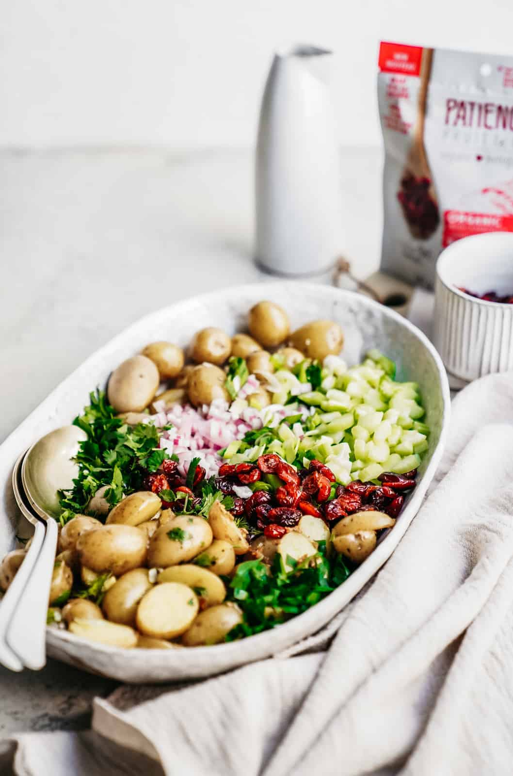 A Vegan Potato Salad Recipe in a big serving dish with fresh herbs.