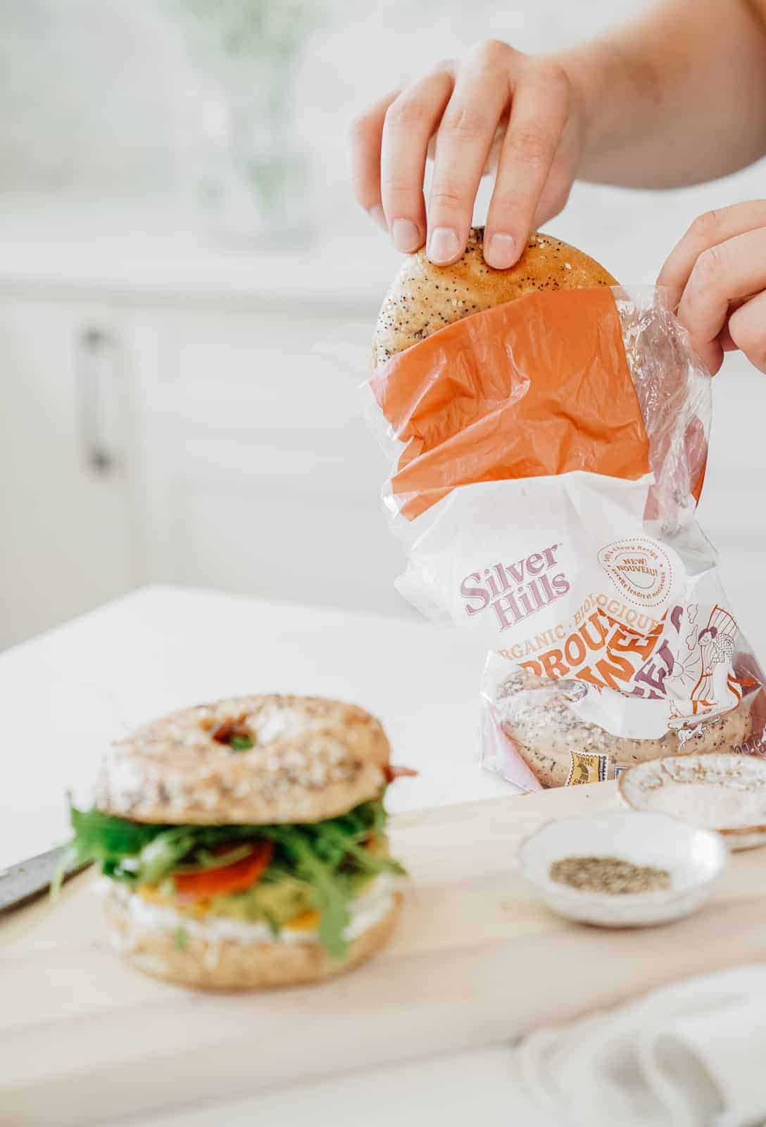 Hand pulling bagel out of bag for a Bagel Sandwich Recipe