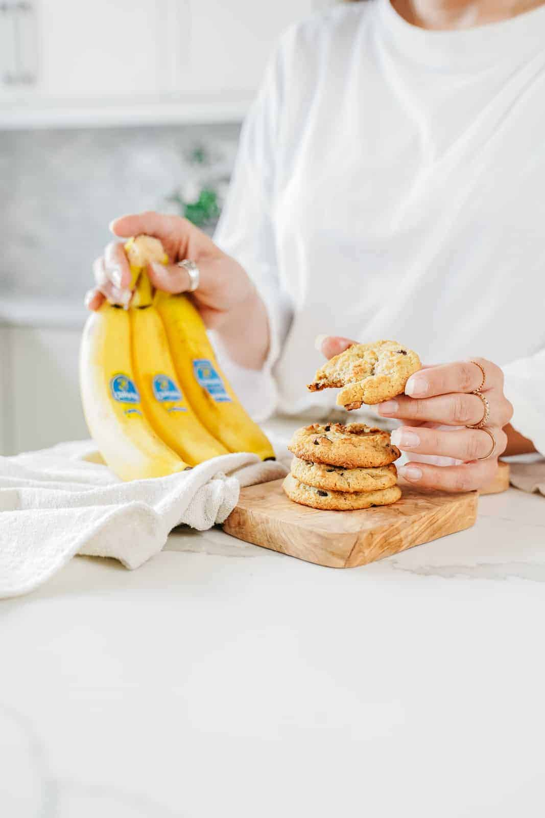 Chiquita Bananas being help on counter with a stack of cookies