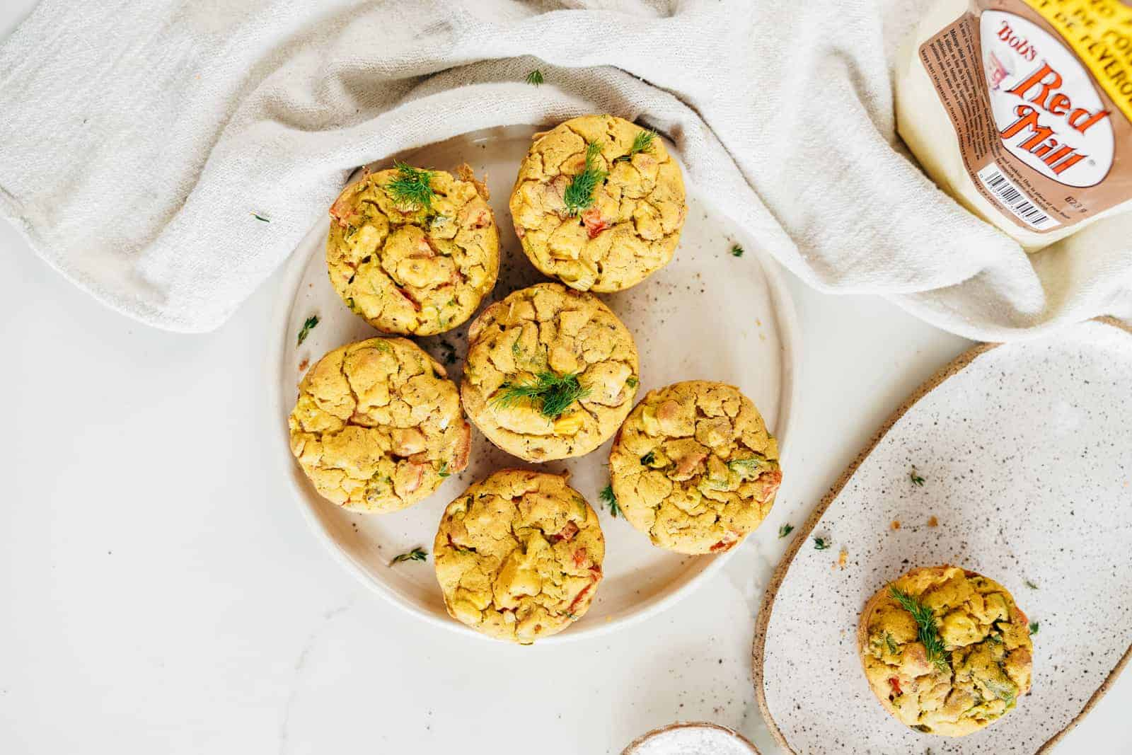 Vegan Chickpea Flour Muffins sitting on a plate with Bob's Red Mill flour in the background.