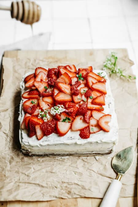 Drizzling honey on top of a Vanilla Honey Cake that is topped with fresh cut strawberries.