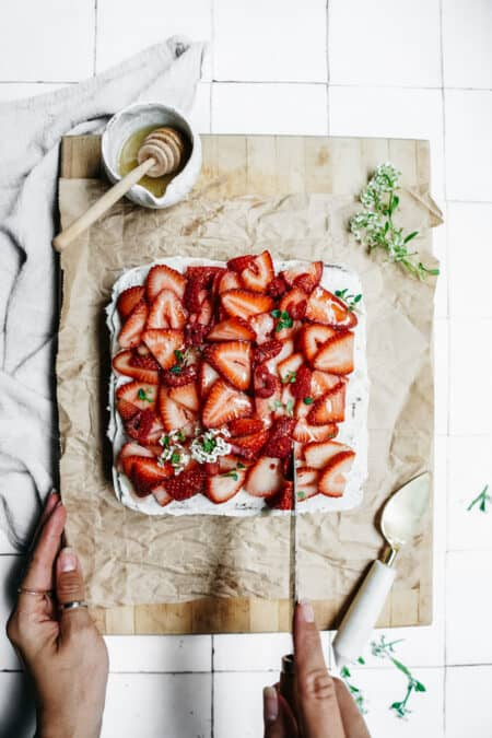Slice of delicious Vanilla Honey Cake made with BeeMaid Honey. Topped with fresh strawberries sitting on parchment paper with a knife about to slice it.