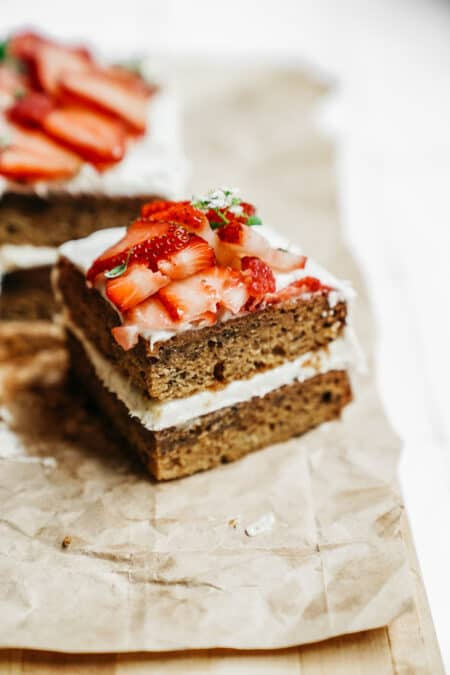 Slice of delicious Vanilla Honey Cake made with BeeMaid Honey. Topped with fresh strawberries sitting on parchment paper.