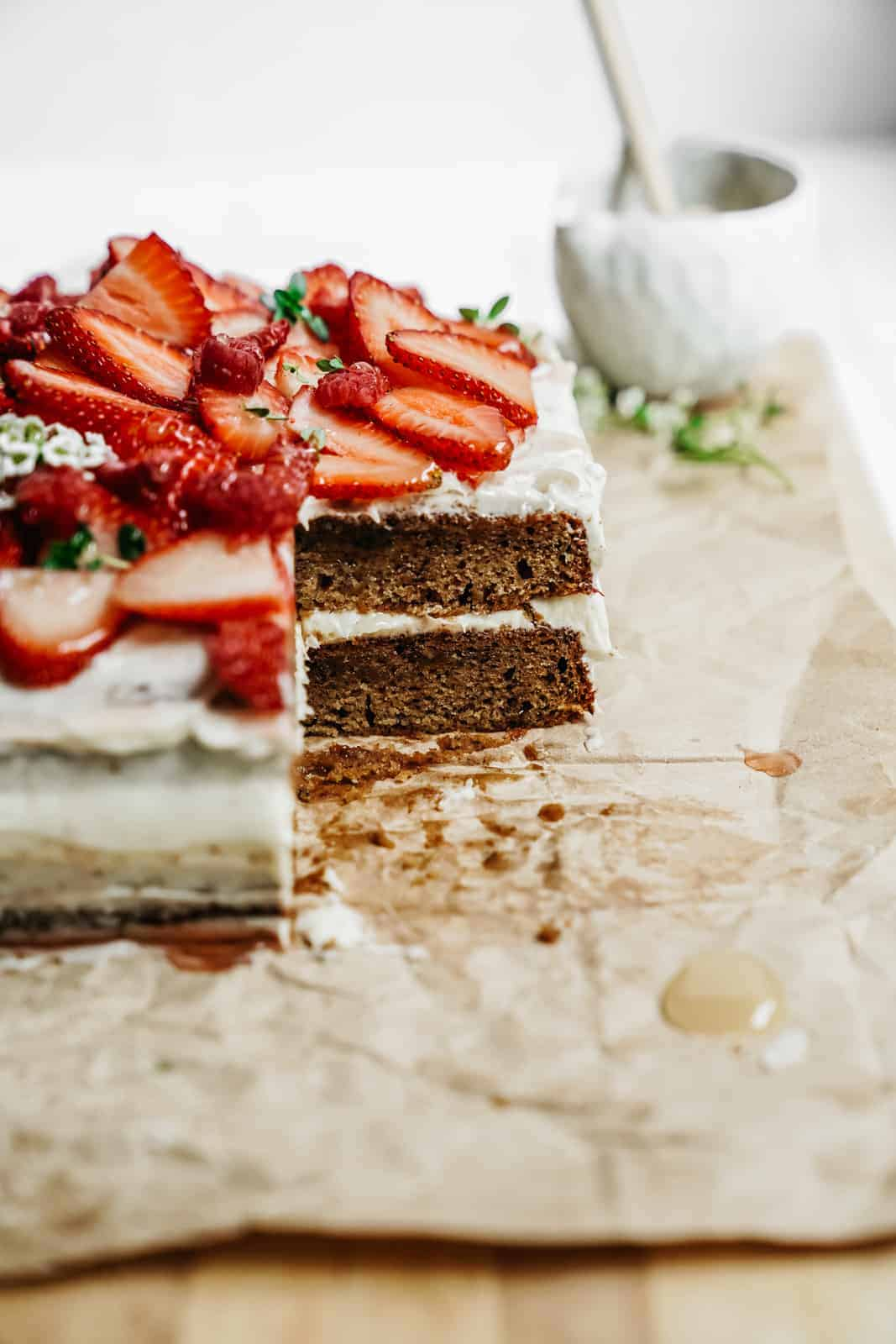Easy Honey Cake with a slice out of it and topped with lush red strawberries.