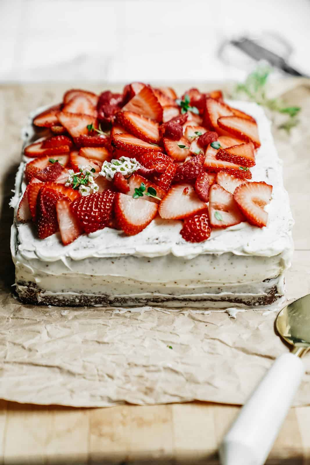 Yummy spring Vanilla Honey Cake sitting on a cutting board with fresh strawberries sliced on top.