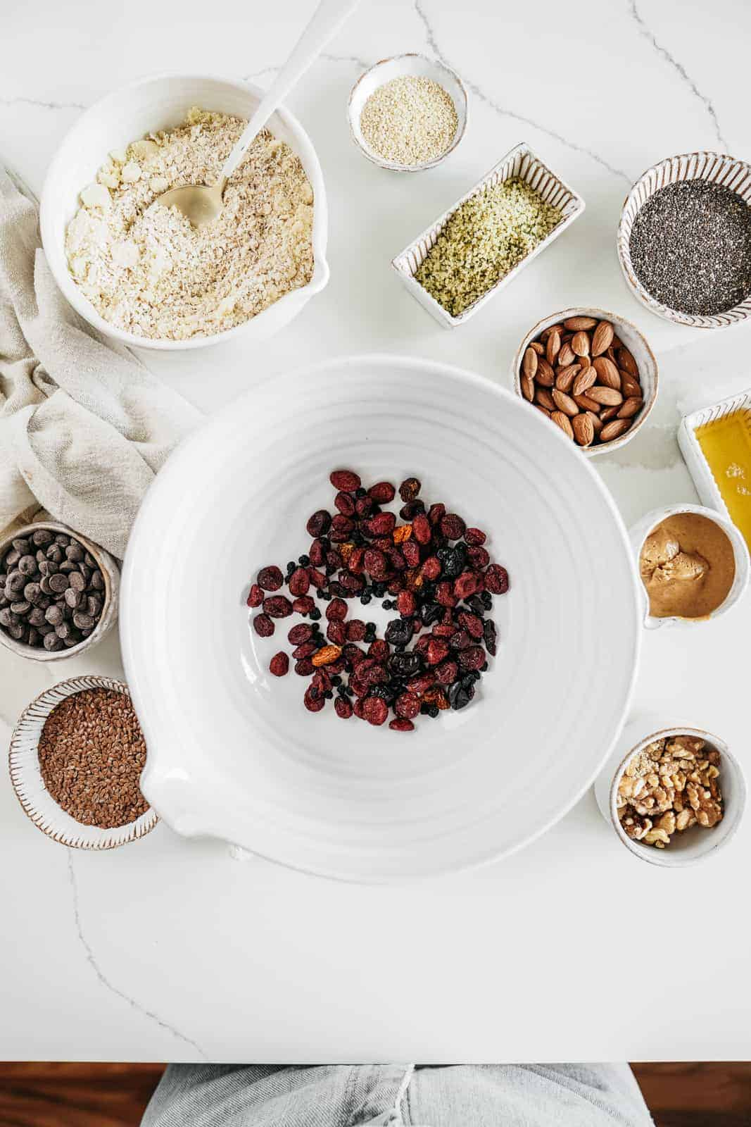 Ingredients for Vegan Granola Bars Recipe laid out on a table with juicy dried cranberries in the centre.
