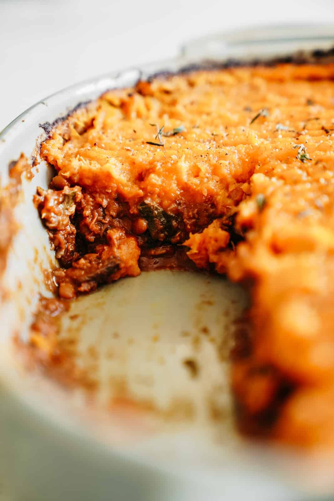 A close-up of a casserole dish with Vegan Shepherd's Pie with a slice removed.